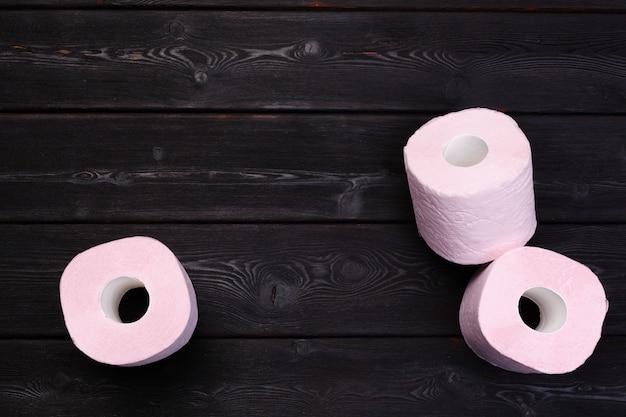 Pastel pink toilet paper rolls on black wooden Premium Photo