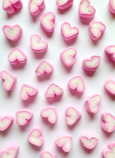 Pastel pink and white heart shaped marshmallow candies scattered on white background Premium Photo