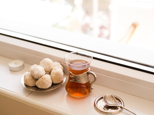 Pastries, tea and spoon in front of window arrangement Free Photo