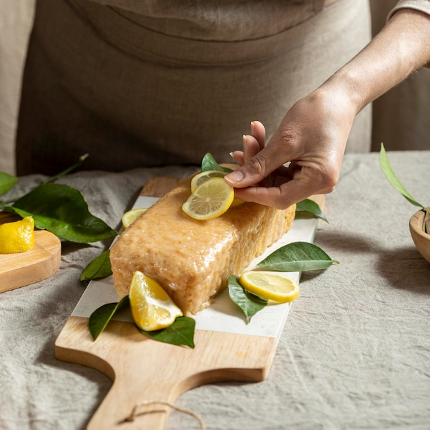 ケーキのトッピングにレモンスライスを追加するパティシエ 無料写真