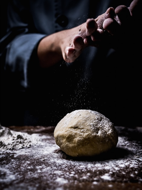 Pastry chef hand sprinkling white flour over raw dough on kitchen table. Premium Photo