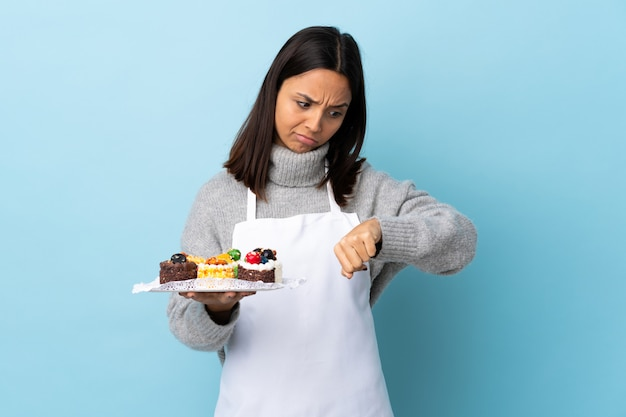 Шеф-кондитер держит большой торт над синей стеной, делая жест опоздания Premium Фотографии