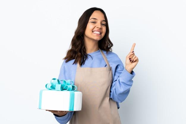 孤立した白い壁に大きなケーキを持って、最高の兆候を示して指を持ち上げるパティシエ Premium写真