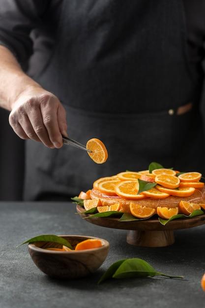 ケーキにオレンジスライスを置くパティシエ 無料写真