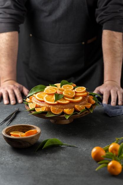 オレンジ色のケーキの後ろに立っているパティシエ 無料写真