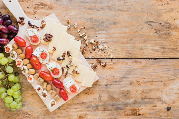 Pastry, sandwiches, tomatoes, walnuts and cheese slices on wooden desk Free Photo
