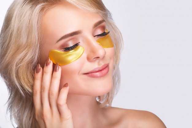 Patch under eyes. beautiful woman face with gold hydrogel patches Premium Photo