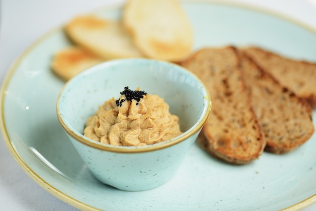 Pate in a bowl with slices of toasted bread Premium Photo