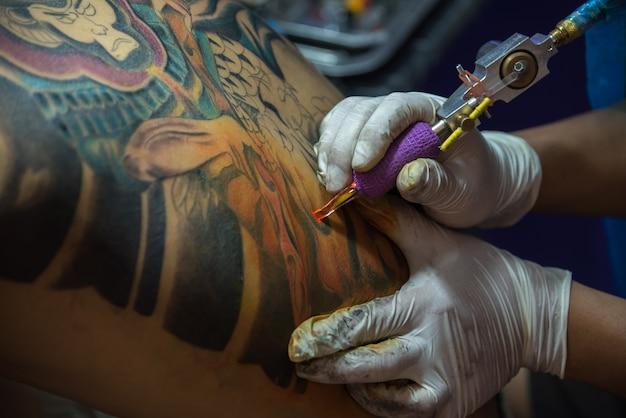 Pathumthani, thailand - 6 мая 2017 года. неопознанный профессиональный художник-татуировщик, рисующий искусство на теле Premium Фотографии