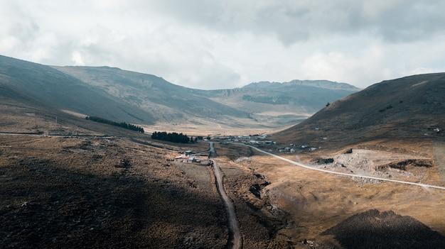 曇り空の下で家の近くの山の真ん中にある経路 無料写真