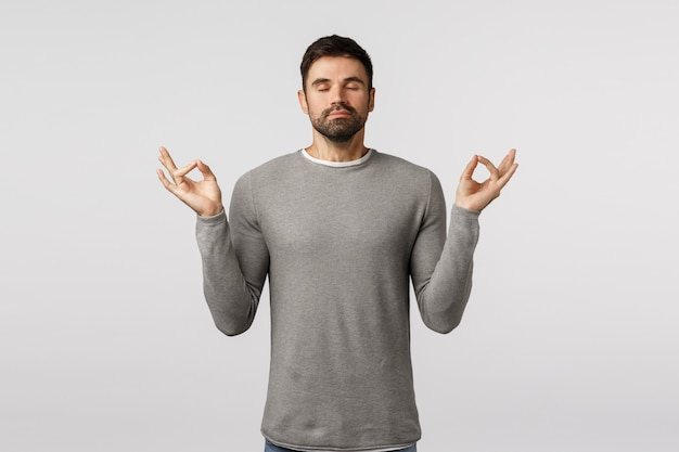 Patience, relaxation and meditation concept. peaceful young handsome bearded guy broaden mind and body, feeling zen, raise hands mudra gesture, practice breathing yoga with closed eyes Premium Photo