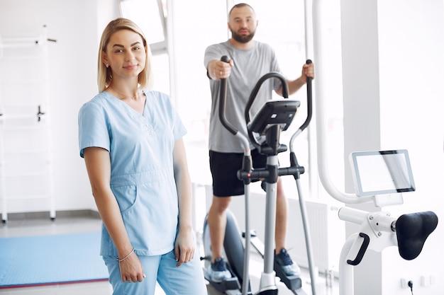 Paziente che fa esercizio su spin bike in palestra con terapista Foto Gratuite