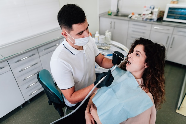 Patient getting teeth cleaning at the dentist Free Photo
