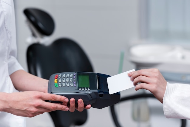 Patient paying for dental treatment with credit card Free Photo