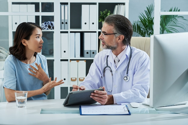 Patient telling doctor about the symptoms of the disease Free Photo