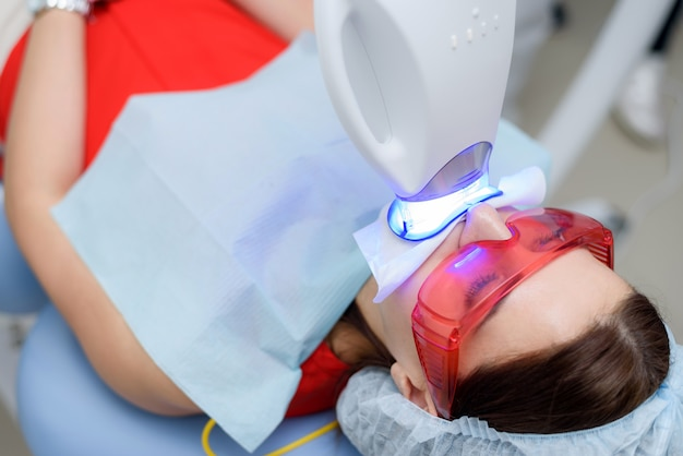 The patient undergoes a procedure for teeth whitening with an ultraviolet lamp Premium Photo