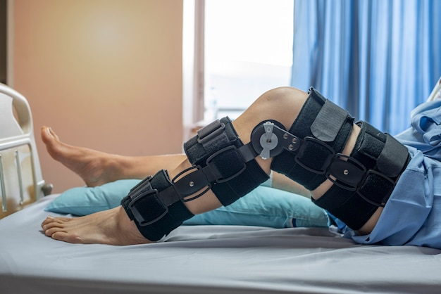 Patient with bandage compression knee brace support injury on the bed in nursing hospital. healthcare and medical support. Premium Photo