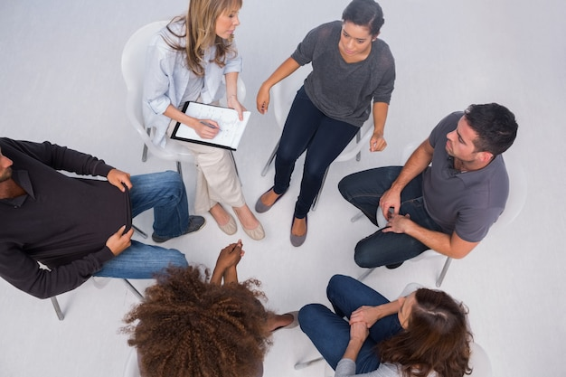 Patients listening to each other in group session sitting in circle Premium Photo
