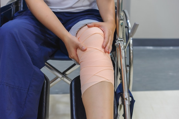 Patients sitting in a wheelchair have pain in the knee that is bandaged. Premium Photo