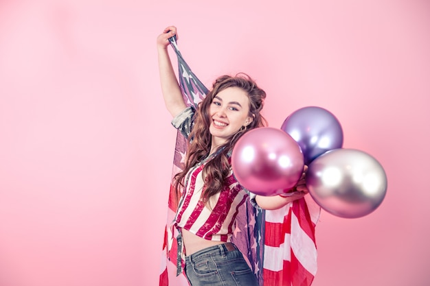 Patriotic girl with the flag of america on a colored background Free Photo