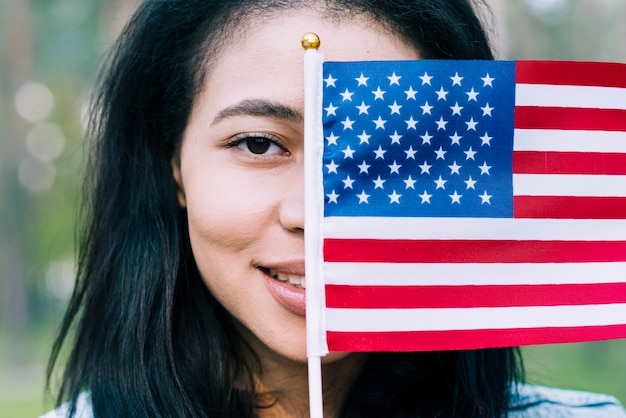 Patriotic woman covering face with usa flag Free Photo