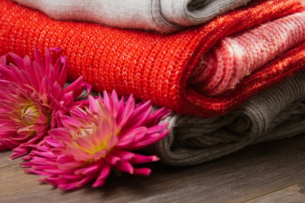 Pattern of colorful knitted sweaters closeup. handmade merino wool product. a stack of folded clothes with flowers. Premium Photo