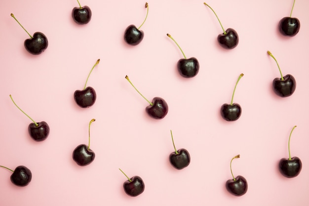 Pattern of dark cherry on pink background top view. flat lay. minimal style. Premium Photo