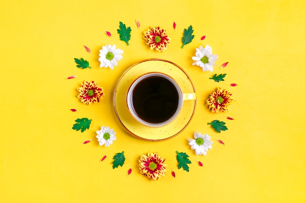 Pattern of flowers of red and white asters, green leaves and cup of hot coffee americano on yellow background flat lay Premium Photo