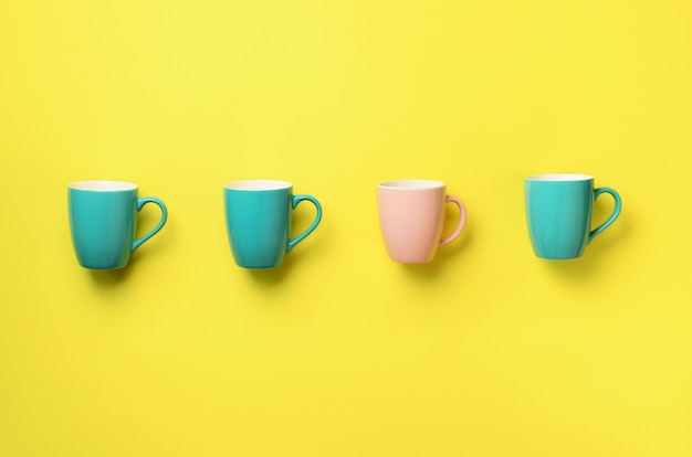Pattern from blue and pink cups over yellow background. birthday party celebration, baby shower concept. Premium Photo