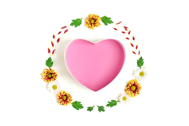 Pattern of gift box shape of heart, flowers yellow, red, white asters, green leaves  isolated on white Premium Photo