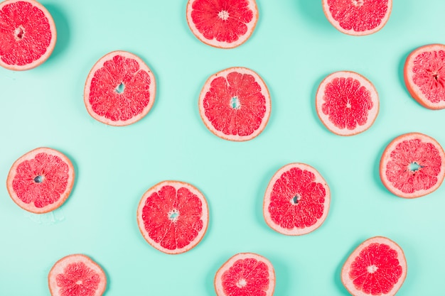 Pattern of grapefruit citrus slices on pastel backdrop Free Photo