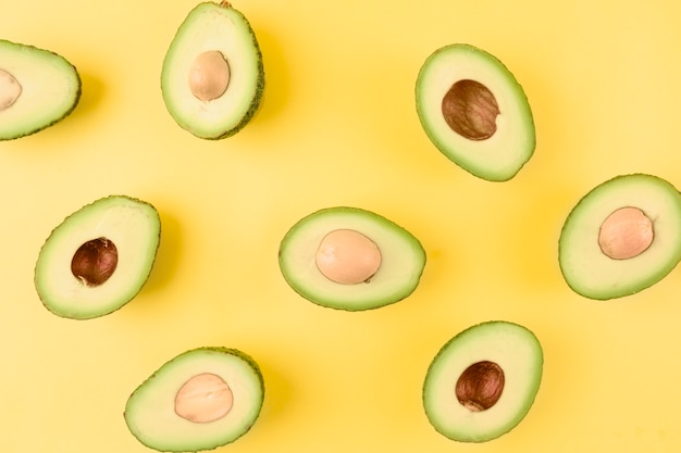 Pattern of halved avocado with seeds on yellow backdrop Free Photo