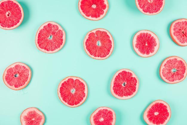 グレープフルーツの柑橘類のスライスのパステル調の背景にスライス 無料写真