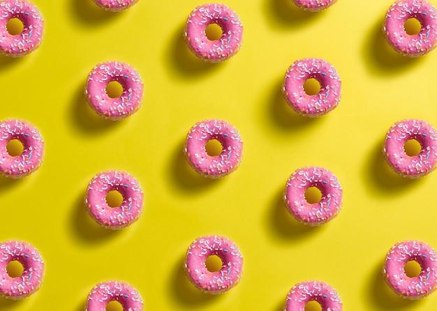 レモン黄色の背景に影付きの色の紙吹雪で飾られたピンクのドーナツのパターン Premium写真