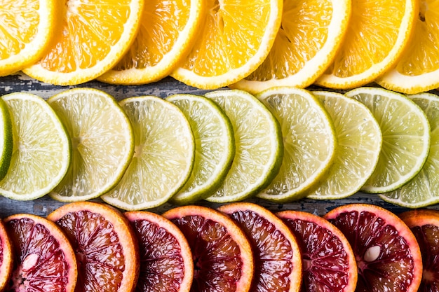 Pattern with fresh slices of different citrus fruit - red and yellow orange fruit, lime, grapefruit. flat lay. Premium Photo