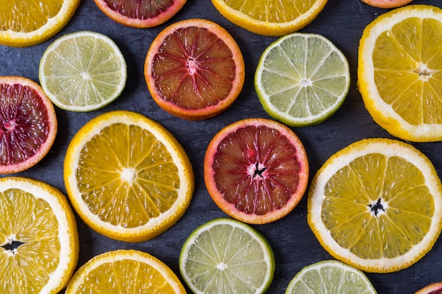 Pattern with fresh slices of different citrus fruit - yellow and red orange, lemon and lime. flat lay. Premium Photo