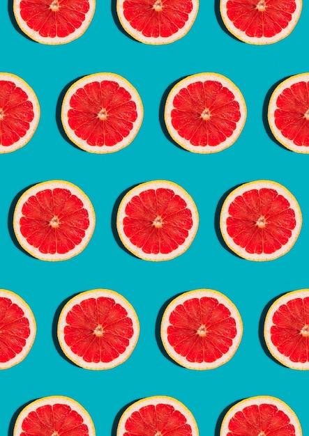 Узор с ломтиком грейпфрута на синем вид сверху плоская планировка. Premium Фотографии