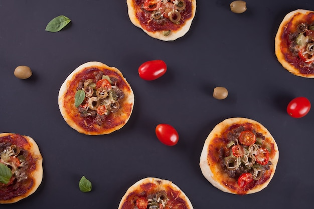 Pattern with homemade mini pizza, cherry tomatoes and green olives on black Premium Photo