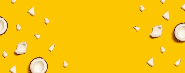 Pattern with ripe coconuts on yellow background. flat lay. Premium Photo