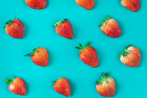 Pattern of yummy strawberries on blue background Free Photo