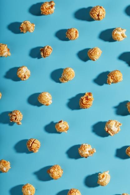 パターンの形で青い背景にキャラメルポップコーンのパターン。 Premium写真