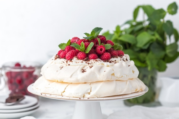 Pavlova cake with raspberries on a white cake stand Premium Photo