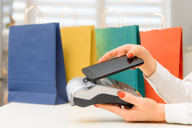 Nfcテクノロジーを使用してスマートフォンで支払う Premium写真