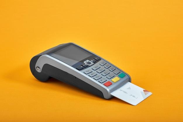 Оплата кредитной картой. терминал на желтом фоне Premium Фотографии