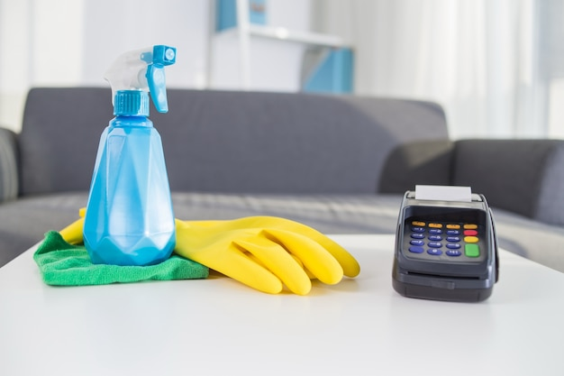 Payment terminal besides spray bottle and rubber gloves Free Photo