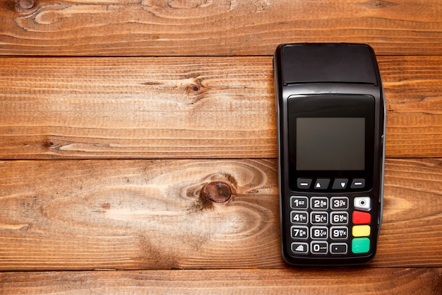 Payment terminal, compact pos terminal on wooden background Premium Photo
