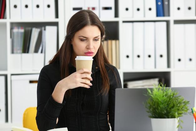 美しいブルネットの笑みを浮かべて店員女性はラップトップpcコンピューターで動作しますお茶の肖像画の腕プラスチックカップを保持します。ホワイトカラー店員労働者職場の仕事提供webチャットワイヤレスソーシャルネットの概念 Premium写真