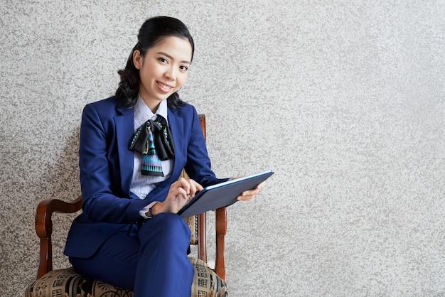 タブレットpcで椅子に座っている笑顔の実業家の肖像画 無料写真