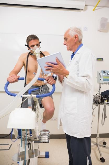 医者、フィットネステストをしている男にタブレットpcを示している Premium写真