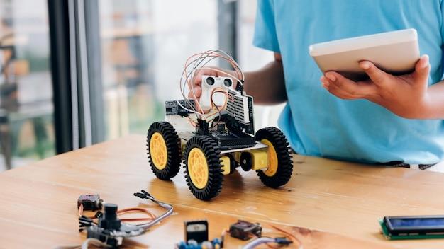 電気おもちゃをプログラミングし、ロボットを構築するタブレットpcコンピューターを持つ少年。 Premium写真